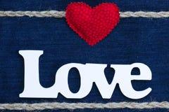 L'amour de mot avec le coeur et la frontière rouges de corde sur le denim Photo libre de droits