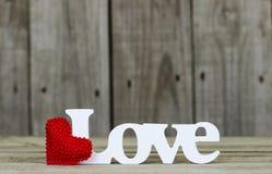 L'amour de mot avec le coeur rouge et le fond en bois Photo stock