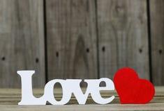 L'amour de mot avec le coeur rouge par le fond en bois Photos stock