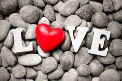 L'amour de mot avec le coeur rouge sur des pierres de caillou Photos stock