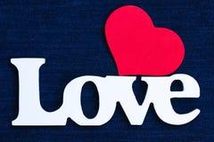 L'amour de mot avec le coeur rouge sur le fond bleu de denim Images stock