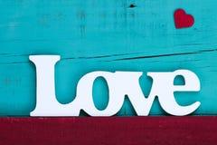 L'amour de mot avec le coeur rouge sur le fond en bois bleu de sarcelle d'hiver Image stock