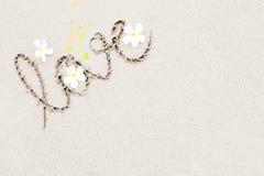 L'amour de mot avec les fleurs blanches sur le backgroun de surface de plage Photographie stock