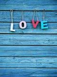 L'amour de mot avec les lettres colorées multi en bois sur le conseil naturel Photographie stock libre de droits
