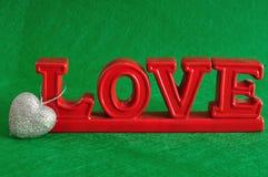 L'amour de mot avec un coeur argenté de scintillement Images stock