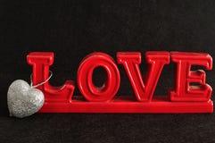 L'amour de mot avec un coeur argenté de scintillement Photos stock