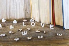 L'amour de mot beaucoup de coeurs sur un fond des livres sur une table en bois Photos stock