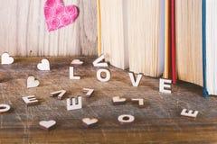 L'amour de mot beaucoup de coeurs sur un fond des livres sur une table en bois Photographie stock libre de droits