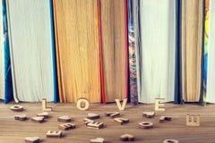 L'amour de mot beaucoup de coeurs sur un fond des livres sur une table en bois Photo libre de droits