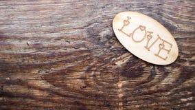 L'amour de mot dans des mains sur un fond en bois Photographie stock