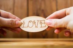 L'amour de mot dans des mains sur un fond en bois Photos libres de droits