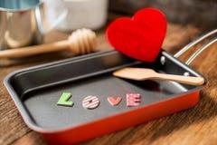 L'amour de mot dans la poêle pour l'amour ou coeur sain Images libres de droits
