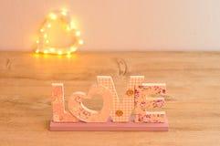 L'amour de mot dans le rose avec hors de la forme de coeur de lumière de foyer Image stock