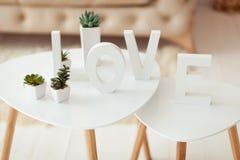 L'amour de mot dans les lettres blanches sur le fond intérieur de volume Sofa et table basse blancs beiges dans la chambre Photographie stock libre de droits