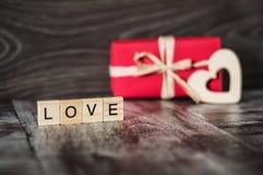 L'amour de mot des briques et d'un cadeau dans la boîte rouge avec un OE Image stock