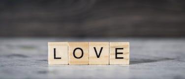 L'amour de mot des cubes en bois sur l'obscurité et le backgro en bois léger Photo stock