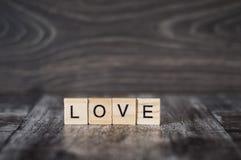 L'amour de mot des cubes en bois sur un fond en bois Photographie stock libre de droits