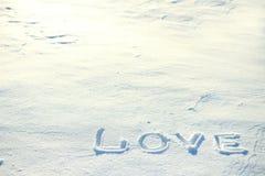 L'amour de mot dessiné dans la neige Photos stock