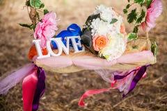 L'amour de mot en bois et fleurs blancs Photos stock