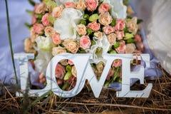 L'amour de mot en bois et fleurs blancs Photographie stock
