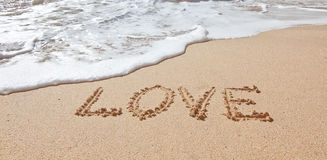 L'amour de mot en mer sur la plage dans le Saint Valentin. Photos stock