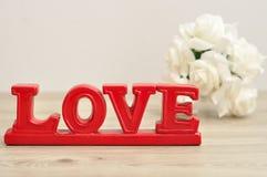 L'amour de mot en rouge avec hors du groupe de foyer de roses Photo stock