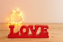 L'amour de mot en rouge avec hors de la forme de coeur de lumière de foyer Photos libres de droits