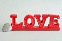 L'amour de mot en rouge avec un coeur argenté Photographie stock