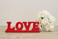 L'amour de mot en rouge avec un groupe de roses blanches Photographie stock libre de droits