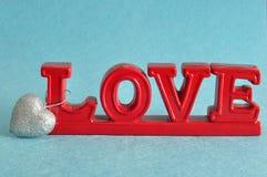 L'amour de mot en rouge avec une forme argentée de coeur Photographie stock libre de droits