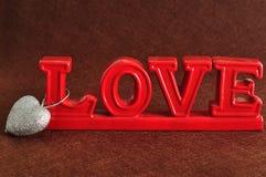 L'amour de mot en rouge avec une forme argentée de coeur Photos stock