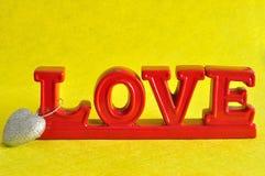 L'amour de mot en rouge avec une forme argentée de coeur Image libre de droits