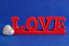 L'amour de mot en rouge avec une forme argentée de coeur Photographie stock