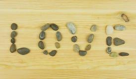 L'amour de mot est présenté des pierres sur le fond en bois Image stock