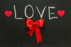 L'amour de mot et l'arc rouge sur le tableau Photo stock