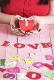 L'amour de mot et une femme tenant un cadeau Images stock