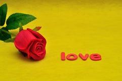 L'amour de mot montré avec une rose artificielle de rouge Photos libres de droits