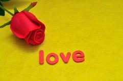 L'amour de mot montré avec une rose artificielle de rouge Image libre de droits