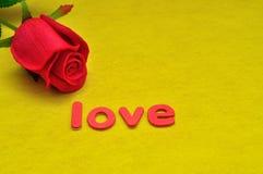 L'amour de mot montré avec une rose artificielle de rouge Photo libre de droits