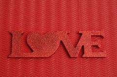 L'amour de mot montré sur un fond rouge Photographie stock