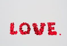 L'amour de mot a orthographié hors de petits coeurs sur un isolat Image stock