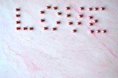 L'amour de mot présenté avec des perles sur le fond texturisé rose Photos stock