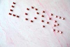 L'amour de mot présenté avec des perles sur le fond texturisé rose Photo libre de droits