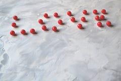 L'amour de mot présenté avec les perles rouges sur le fond texturisé Image libre de droits