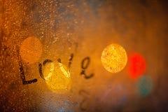 L'amour de mot sur la fenêtre sous la pluie Photos libres de droits