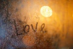 L'amour de mot sur la fenêtre sous la pluie Image stock
