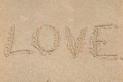 L'amour de mot sur la plage avec la vague Photographie stock