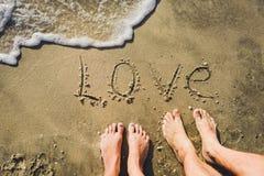 L'amour de mot sur la plage avec la vague Photos stock