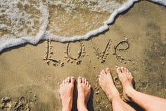 L'amour de mot sur la plage avec la vague Images libres de droits