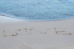 L'amour de mot sur la plage avec la vague photo stock